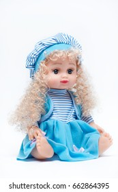 Baby doll in blue dress on white background