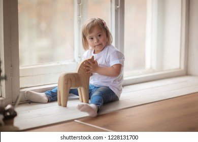 baby with Down syndrome plays on the table with a wooden toy, the window in the real interior