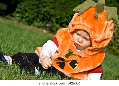 Baby dressed in halloween costume sitting on grass in sunlight