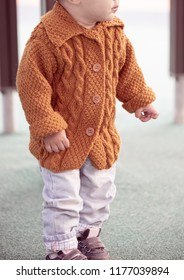 Baby dressed in knitted handmade cardigan