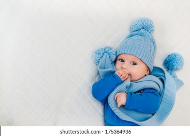 baby dressed in winter scarf and cap