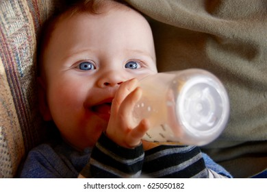 Baby drinking from a bottle and smiling