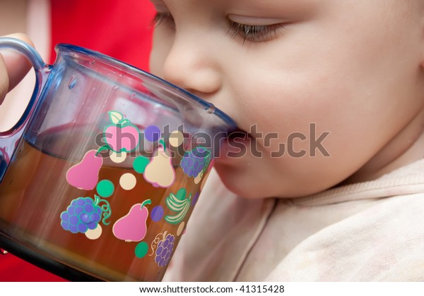 Baby drinking juice from a cup