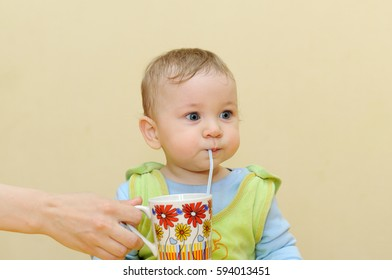 Baby drinks juice through a straw from a cup that holds mom