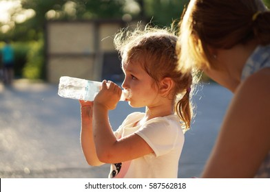 Baby drinks water from bottle.