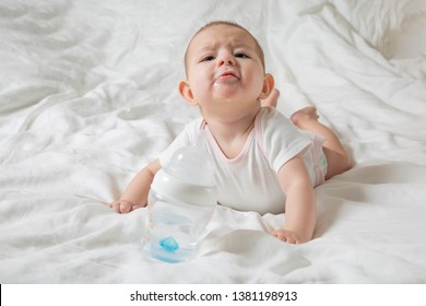 The baby is drooling and teething. He lies on a white bed and pulls his hands to a bottle of water. Cheerless and naughty child.