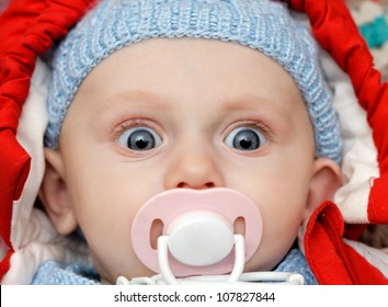 baby with dummy making a funny surprised face