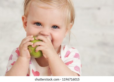 Baby eat an organic green apple - fresh apple as perfect healthy finger food for little ones