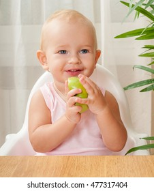 Baby eating an apple in the kitchen. Feeding baby.