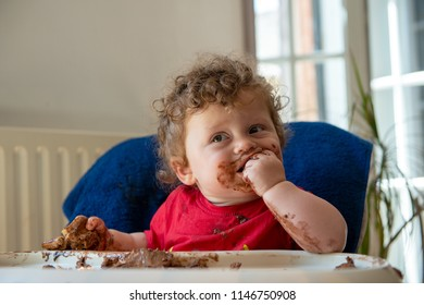 a baby is eating a chocolate cake