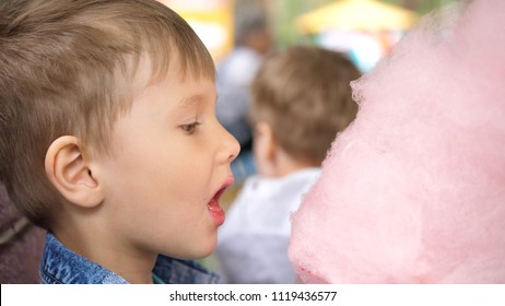 Baby eating cotton candy in the Park. Sweet and airy dessert