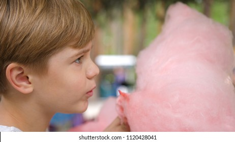 Baby eating cotton candy in the Park. Sweet and airy dessert. The day of the birth of the child.