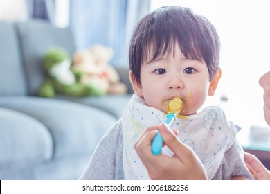 Baby eating food at home. Mother feeding a baby. Asian boy.