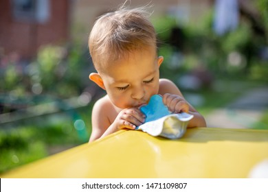 baby eating fruit puree in pouch and looking into the food in front of the yellow table. on the background is a green garden on a sunny day in blur
