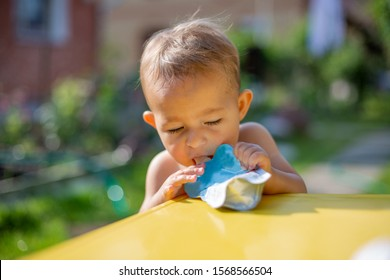 baby eating fruit puree in pouch and close eves enjoying in front of the yellow table. close up, on the background is a green garden on a sunny day in blur