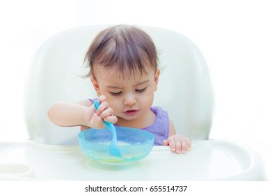 baby eating in the kitchen on the sittting on the table