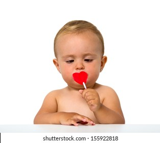 baby eating lollipop isolated on white