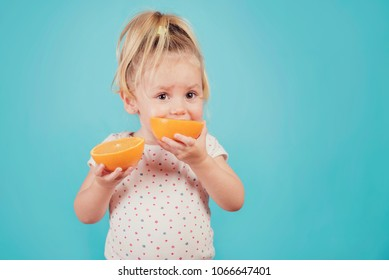 baby eating an orange on blue background