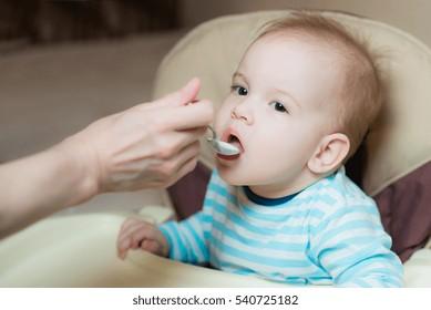 baby eating from a spoon eats milk porridge