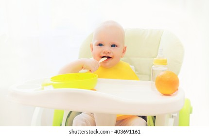 Baby eating spoon food at the table home