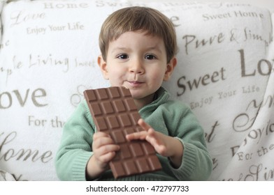 baby eating a tablet of chocolate