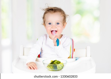 Baby eating vegetables sitting in white high chair. Solid food for infant. Little girl eating healthy vegetable lunch of steam cooked broccoli. Nutrition for toddler and preschooler. Kids eat fruit.