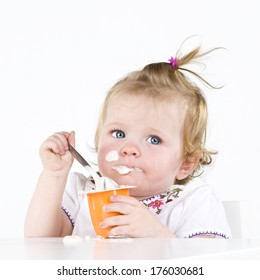 A baby eating yogurt with some on her face.