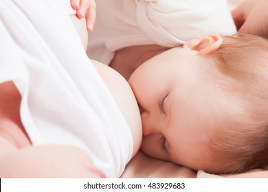 The baby eats breast milk mom lying on bed