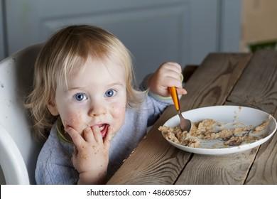 Baby eats porridge spoon mashed