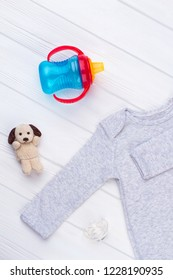 Baby essentials on wood. Top view, bottle, pacifier and plush dog. White wood background.