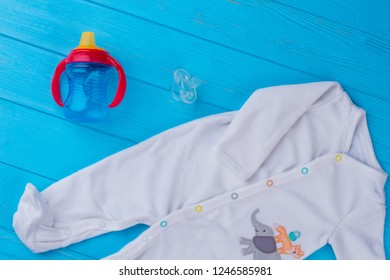 Baby essentials, white wool pajama, bottle and pacifier. Blue wood background.