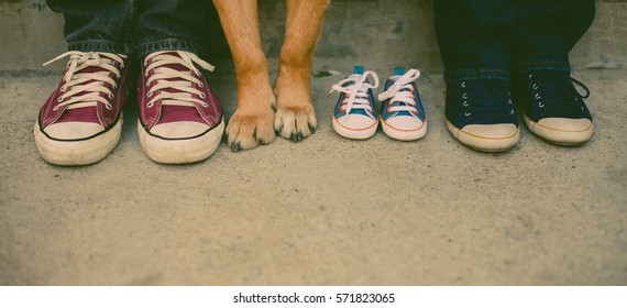 baby expecting picture with mother, father and the family dog's feet.