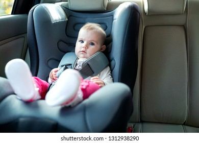 Baby exploring her car seat with great curiosity