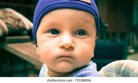 Baby face close up.Seven-month-old white child with blue eyes in blue hat outdoor.