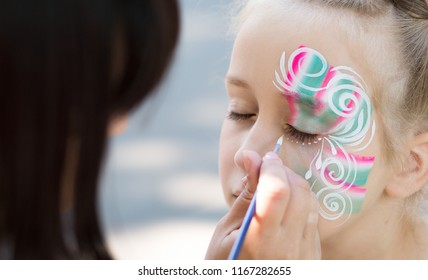 Baby face painting. Woman artist painting face of kid outdoors, copy space