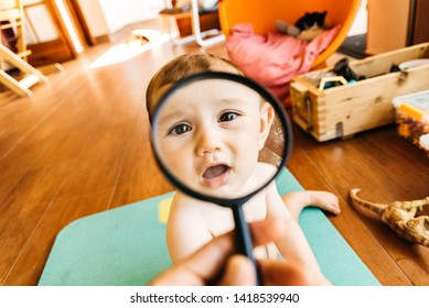 Baby face while playing with a magnifying glass, which makes a funny and tender face.