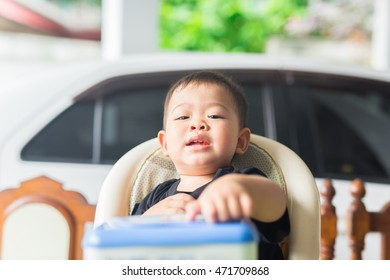 baby facial expression after meal. he is very happy because he is full. he is sitting alone on high chair.