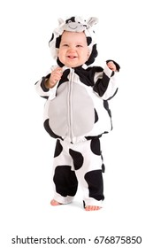 A baby in a fancy dress cow costume on a white background