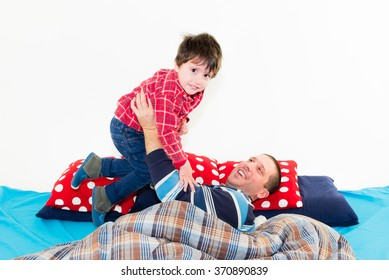 Baby and father playing together on the bed