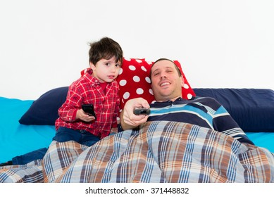 baby and father watching tv together on the bed