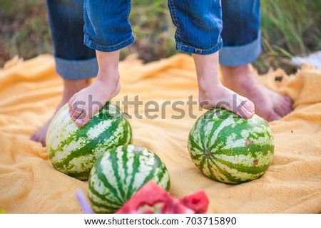 9b7bae4290b Baby and father s legs and a lot of watermelons. The child is standing on  watermelons