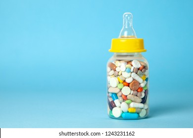 Baby feeding bottle filled with pills. With mother's milk, the child gets everything the mother eats. Copy space for text