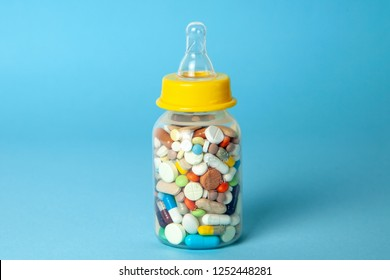 Baby feeding bottle filled with pills. With mother's milk, the child gets everything the mother eats. closeup