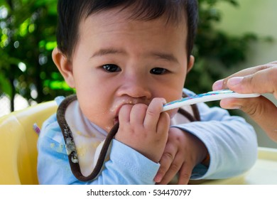 baby feeding spoon handle into his mouth.
