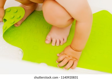 Baby feet in bathtub on anti slip rubber mat for bathroom
