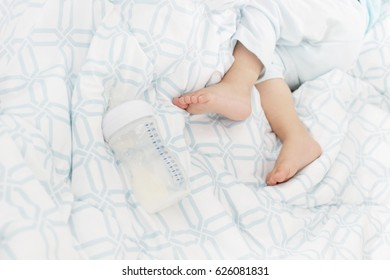 Baby feet with bottle on the bed / Baby with bottle while sleeping