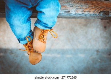 baby feet in fashionable jeans and shoes on the bench