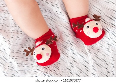 Baby feet in funny Chtistmas socks.Happy holidays and Happy New Year.