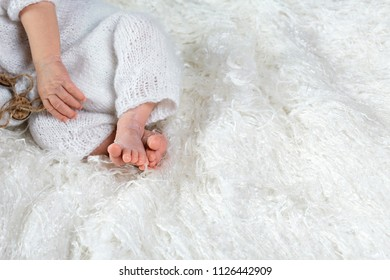 Baby feet and hands, isolated on white, on a white textile background, the concept of a new life, copy space.