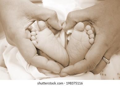 Baby feet in heart shaped hands